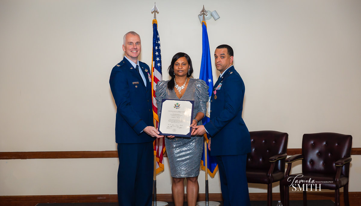 Air Force Spouse receiving spouse appreciation certificate.
