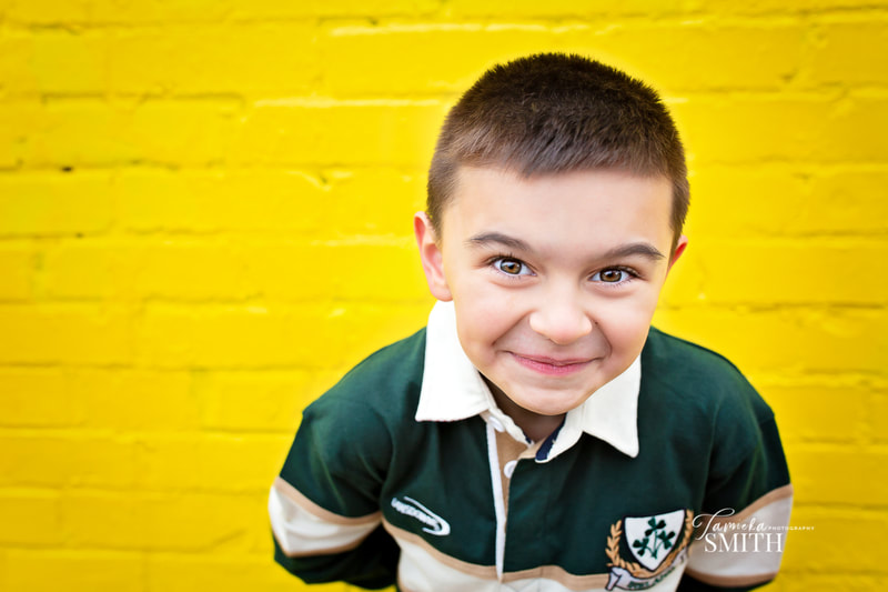 Seven year old boy posing near yellow wall in Old Town Alexandria